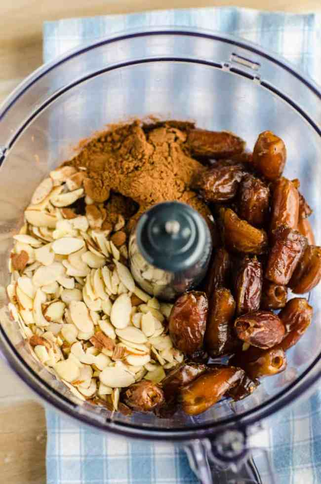 The bowl of a food processor is filled with sliced almonds, pitted whole dates, and cocoa powder for Chocolate Mint Energy Bites - The Goldilocks Kitchen
