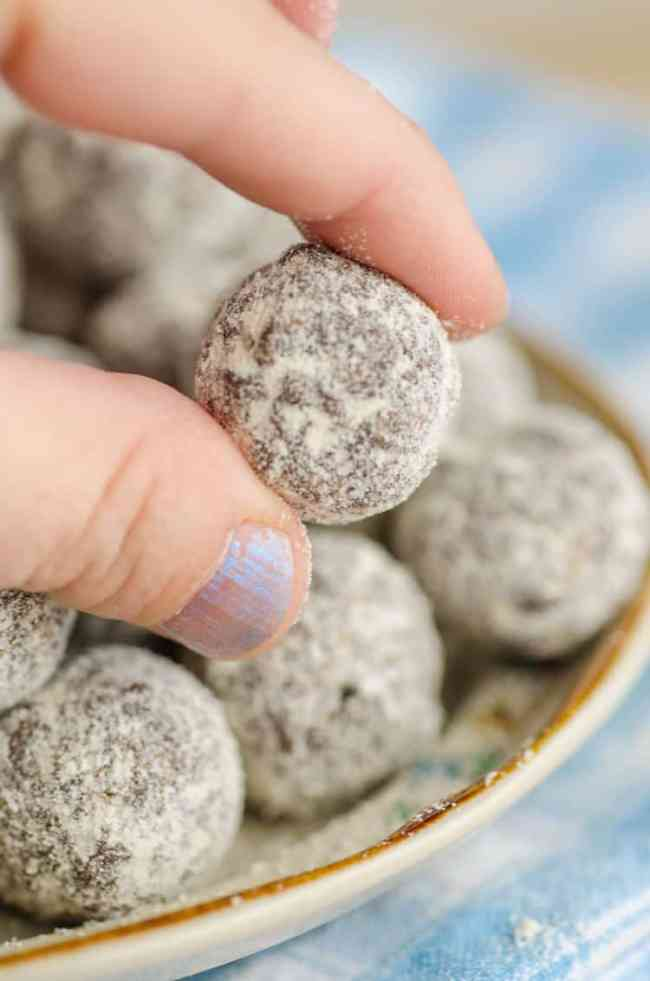 A Chocolate Mint Energy Bites ball is held close to the camera by fingers to show the texture - The Goldilocks Kitchen