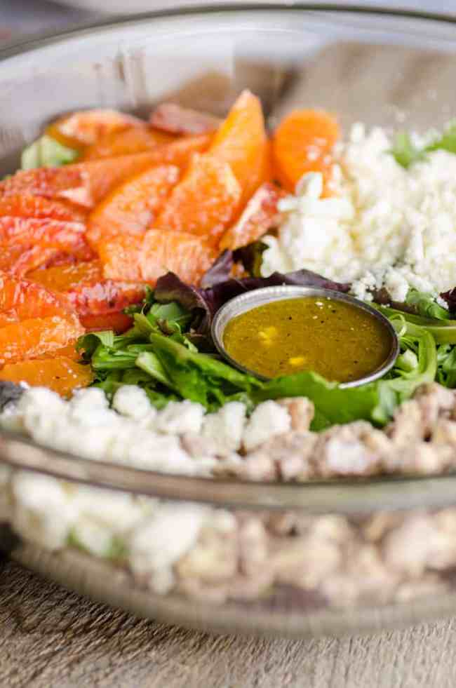 A large salad bowl with ingredients for Feta Citrus Salad arranged in groups with a small cup of dressing in the middle - The Goldilocks Kitchen