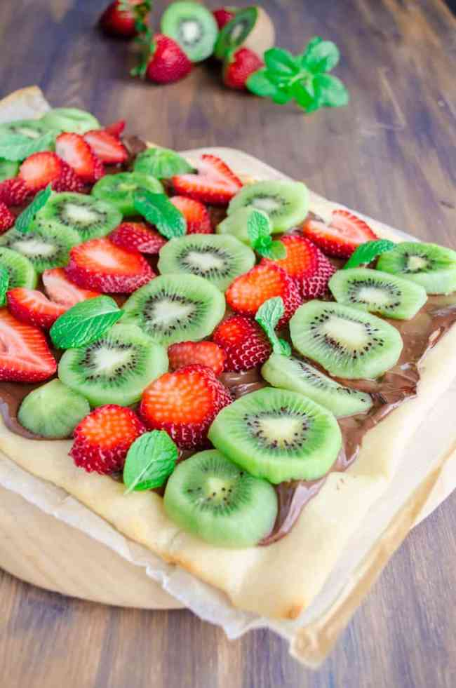 A Nutella Pizza sits on a wooden pizza peel, topped with slices of fresh strawberries and Kiwi with mint leaves sprinkled in here and there - The Goldilocks Kitchen
