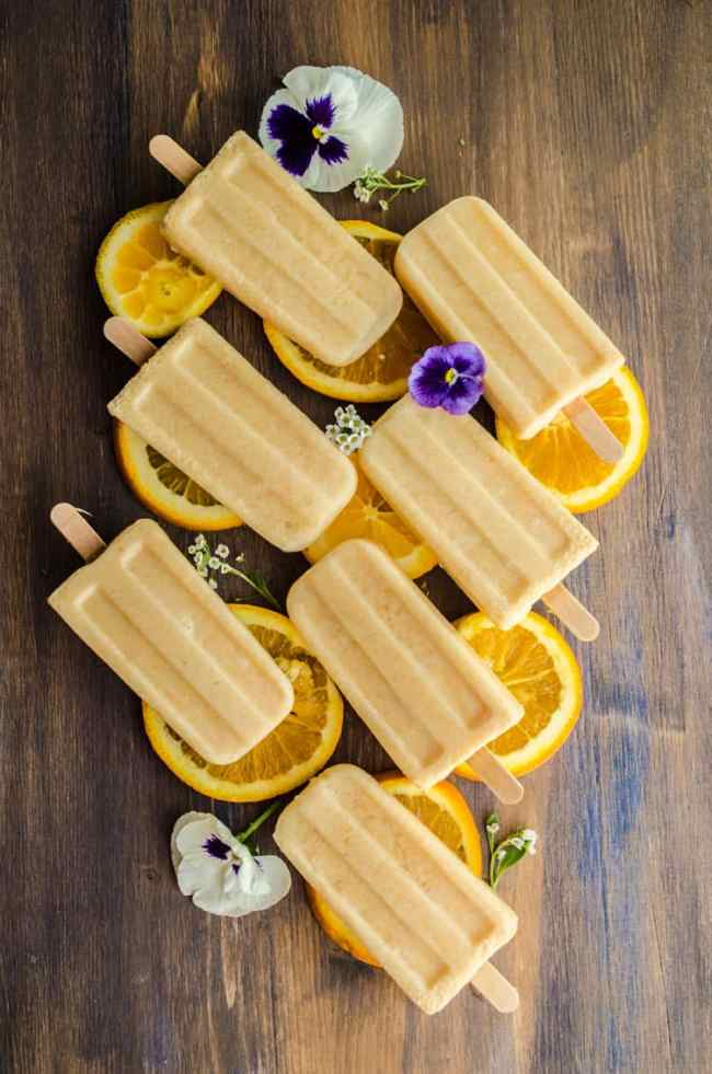 A view looking down on seven Orange Creamsicle Smoothie Pops arranged diagonally, sitting on top of orange slices and surrounded with a few flowers - The Goldilocks Kitchen