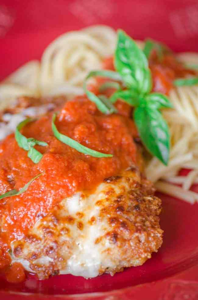 A closeup of Easy Chicken Parmesan on a red plate with a side of spaghetti and some fresh basil for garnish.