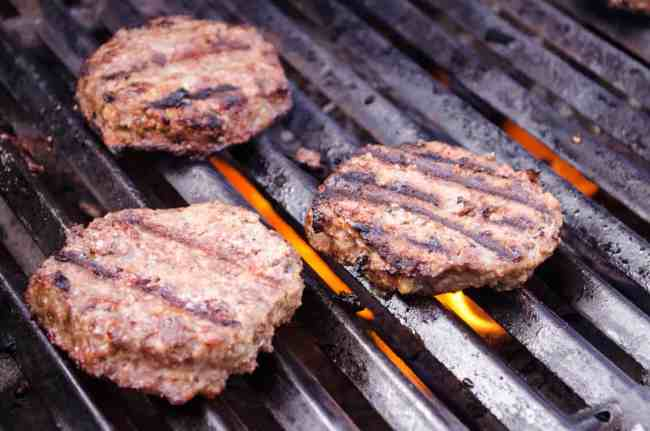 Meatloaf Burgers cook on a gas grill.