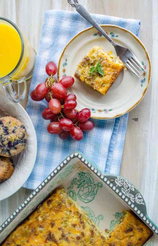Make ahead breakfast Green Chile Breakfast Cubes or 'Chile Cubes' casserole sits on a wooden table top with grapes, orange juice, blueberry muffins and a casserole dish.