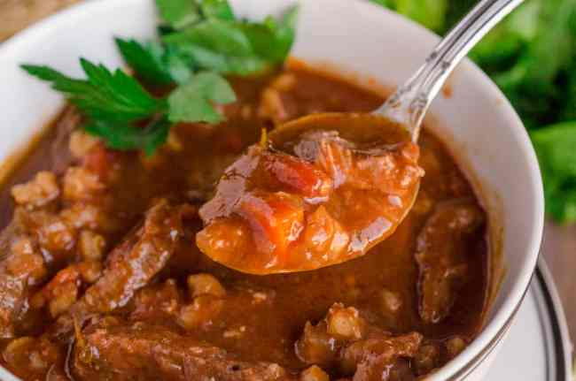 Closeup of a spoon full of Slow Cooker Beef and Barley Stew over a bowl.