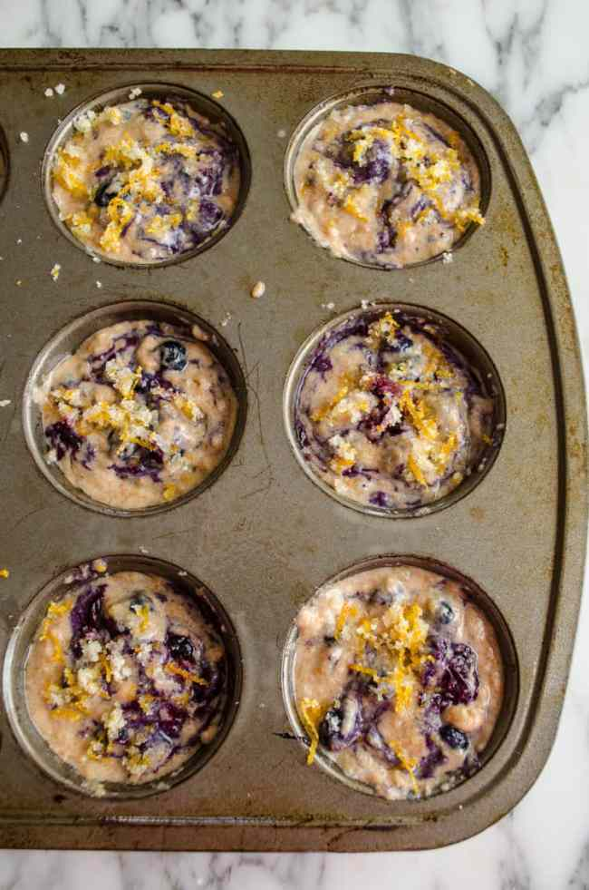 A streusel make of lemon zest and sugar is sprinkled over the tops of each cup of Moist Whole Wheat Blueberry Swirl Muffins batter.