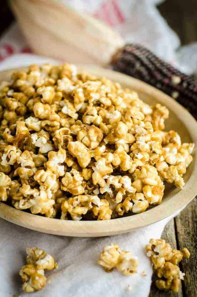 A wooden bowl sits on a wooden table filled with Microwave Caramel Popcorn - The Goldilocks Kitchen