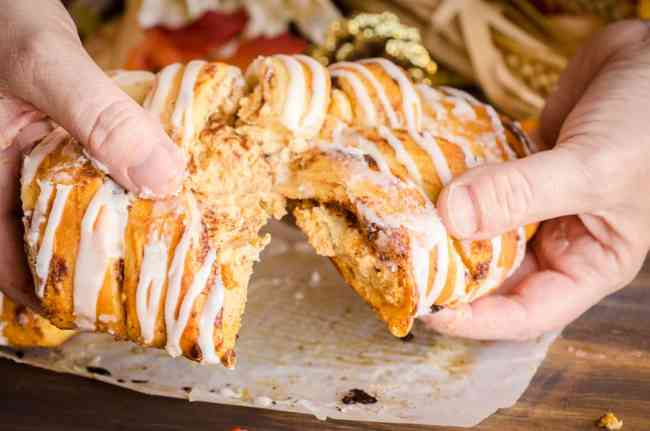 A Pumpkin Pie Breakfast Braid being pulled apart to show the pumpkin cream cheese filling- The Goldilocks Kitchen