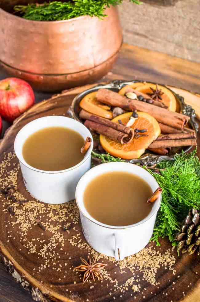 Mugs of Mulled Apple Cider a.k.a. Wassail sit on a wooden table surrounded by sugar, mulling spices and orange slices.