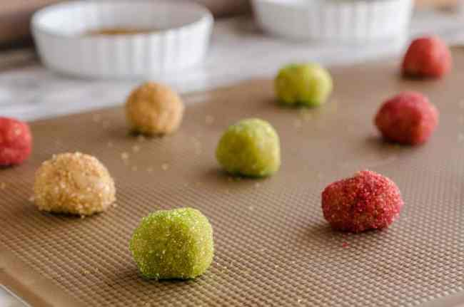 Cookie dough balls rolled in green, brown and red sugar crystals sit on a cookie sheet waiting to become Dove Peanut Butter Buttons cookies - The Goldilocks Kitchen