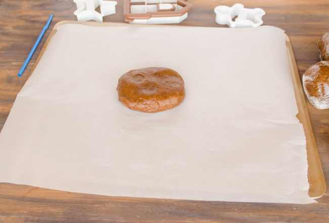A disc of Easy Gingerbread Cookies dough sits on parchment paper surrounded with cookie cutters - The Goldilocks Kitchen