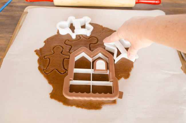 Cookie cutters are used to cut shapes out of rolled out Easy Gingerbread Cookies dough- The Goldilocks Kitchen