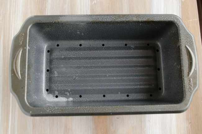 A picture of a meatloaf pan sprayed with non-stick cooking spray for Meatloaf - The Goldilocks Kitchen