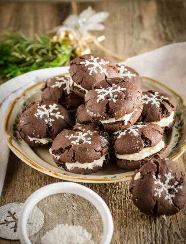 Homemade Oreo Cookies sit on a small plate on a wooden tabletop, decorated with powdered sugar stencils of snowflakes on top - The Goldilocks Kitchen
