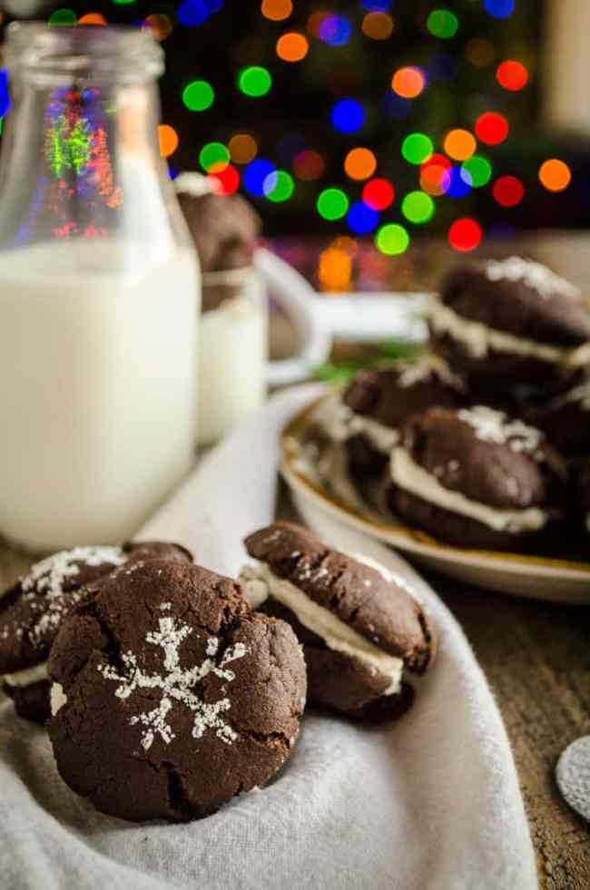 A closeup of Homemade Oreo Cookies with a jug of milk and Christmas lights in the background - The Goldilocks Kitchen