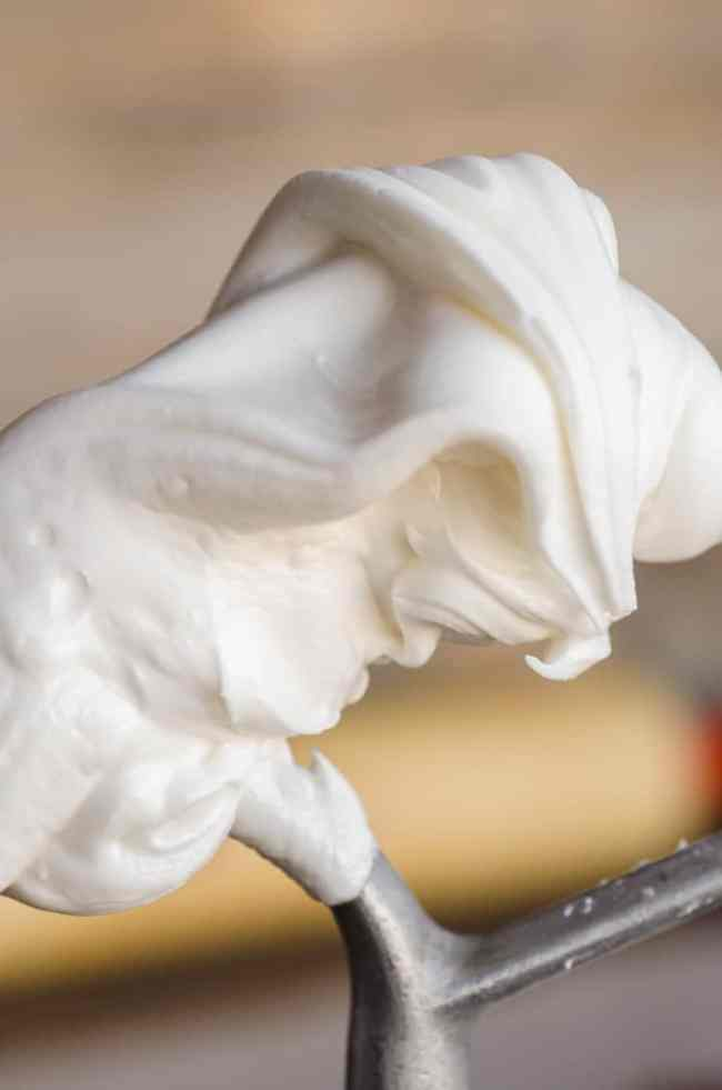 A close up picture of flowing white Royal Icing Gingerbread Frosting on the end of a stand mixer beater - The Goldilocks Kitchen