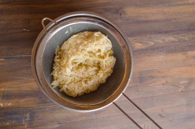 Shredded apple sits in a sieve over a bowl to allow excess liquid to drain to make Easy Apple Turnovers - The Goldilocks Kitchen