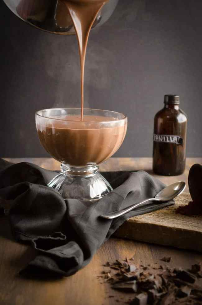 Steaming hot Homemade Chocolate Pudding is poured from a stainless steel pot into a decorative glass serving bowl - The Goldilocks Kitchen