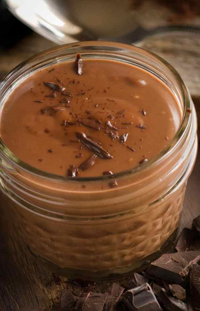 A small decorative mason jar full of Homemade Chocolate Pudding, sprinkled with chocolate shavings on top - The Goldilocks Kitchen