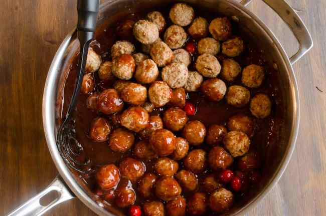 Meatballs are stirred around in a stainless steel pan with sauce to make Cranberry Ginger Meatballs - The Goldilocks Kitchen