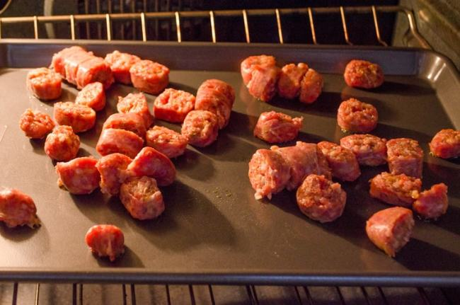 Chopped sausage links cooking on a sheet pan for 30 Minute Italian Sausage Sheet Pan Dinner - The Goldilocks Kitchen