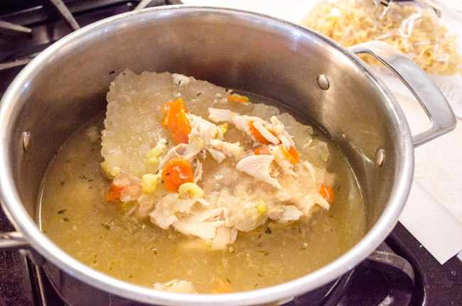 Frozen Make Ahead Chicken Noodle Soup thawing out in a pot - The Goldilocks Kitchen