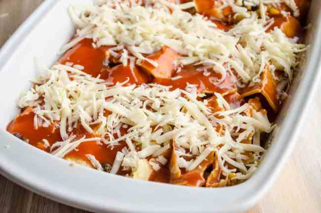 Black Bean Sweet Potato Enchiladas sit in a baking dish ready to be baked in the oven - The Goldilocks Kitchen