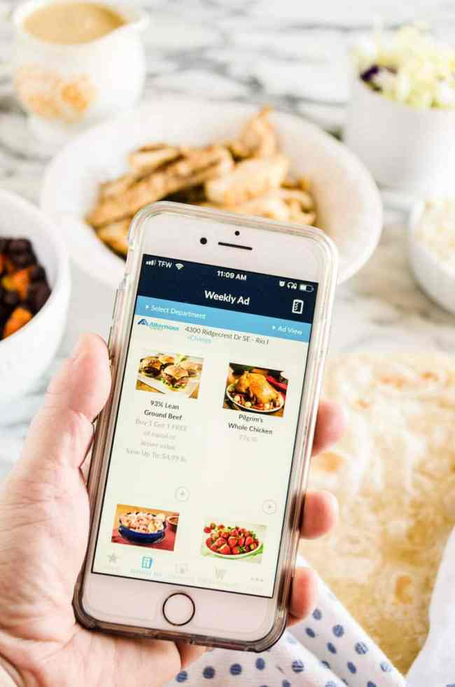 An iPhone is held close to the camera showing coupons on the screen for ingredients to make Grilled Chicken Tacos with Green Chile Cream Sauce - The Goldilocks Kitchen