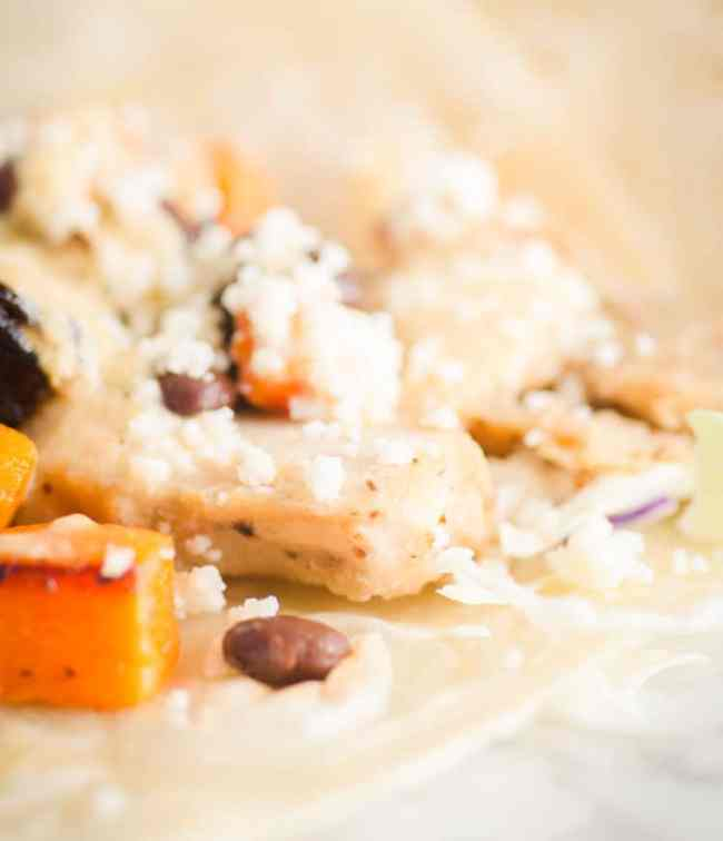 A close up picture of a Grilled Chicken Taco with Green Chile Cream Sauce showing chicken, black beans, roasted squash, green chile cream sauce, shredded cabbage and crumbled queso fresco - The Goldilocks Kitchen
