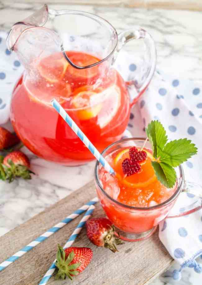 A glass pitcher full of strawberry lemonade with lemon slices floating on top next to a glass of lemonade garnished with heart shaped strawberry slices, strawberry leaves and a blue and white striped straw for Fresh Sparkling Strawberry Lemonade - The Goldilocks Kitchen