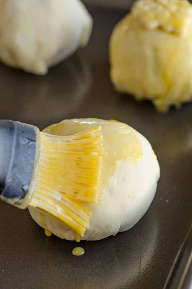 Beaten egg is brushed over a ball of dough (with a meatball inside) to make Easy Meatball Wellingtons - The Goldilocks Kitchen