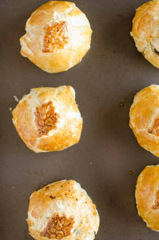 Freshy baked golden brown Easy Meatball Wellingtons sit in a row on a rimmed baking sheet. - The Goldilocks Kitchen