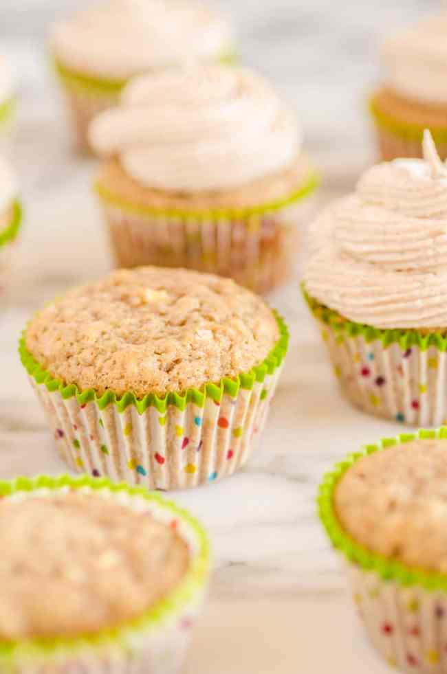 Apple Cinnamon Cupcakes sit on a marble counter, some frosted some plain. - The Goldilocks Kitchen
