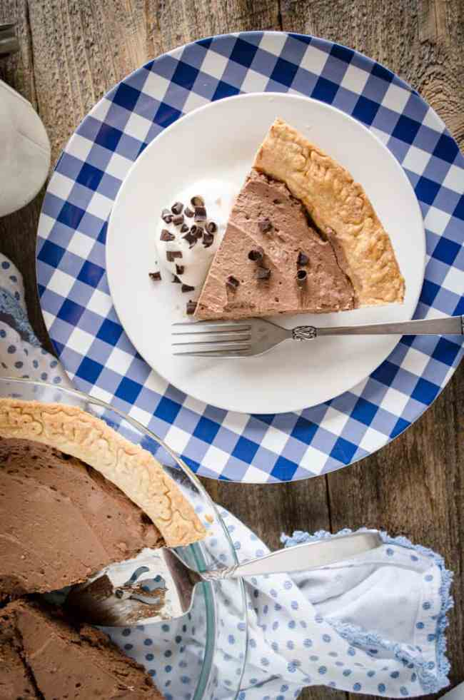 A slice of French Silk Pie without Raw Eggs sits on a blue and white gingham plate garnished with chocolate curls- The Goldilocks Kitchen