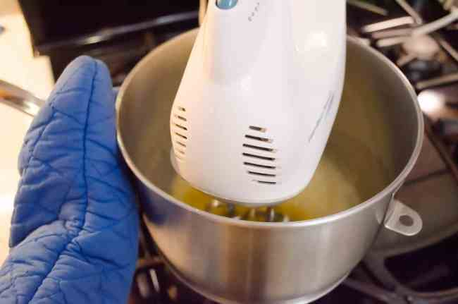 A hand held mixer beats egg whites in a metal bowl set over a pot of simmering water to cook the egg whites to make French Silk Pie without Raw Eggs - The Goldilocks Kitchen