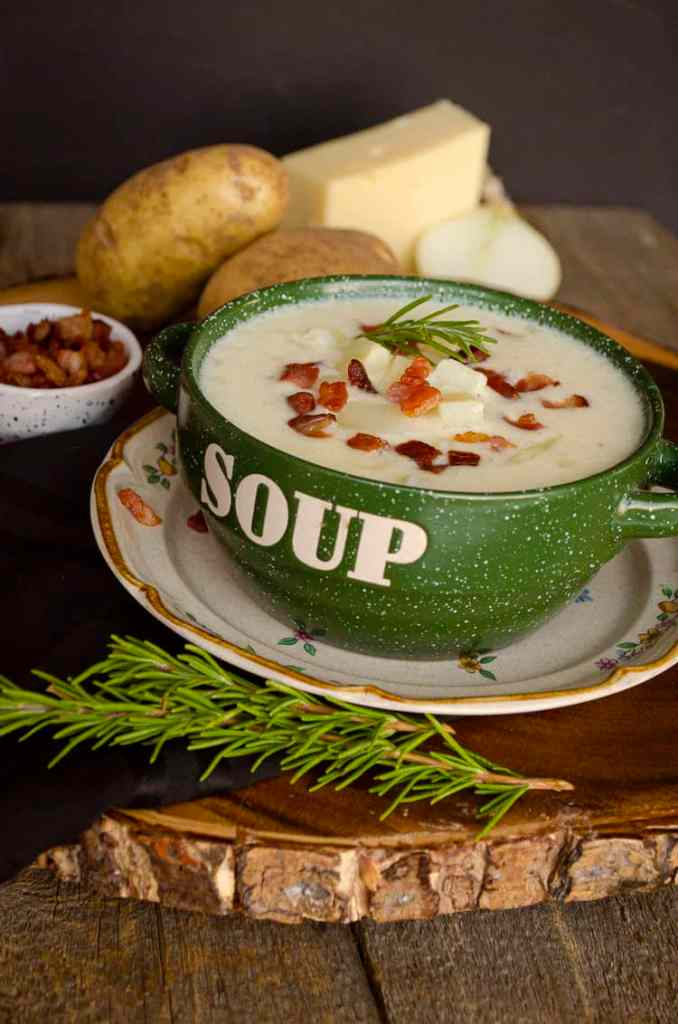"Looing at a green bowl with the word ""soup"" on it's side, filled with Gluten-free Swiss Potato Soup and surrounded by ingredients such as swiss cheese, raw potatoes and onion."