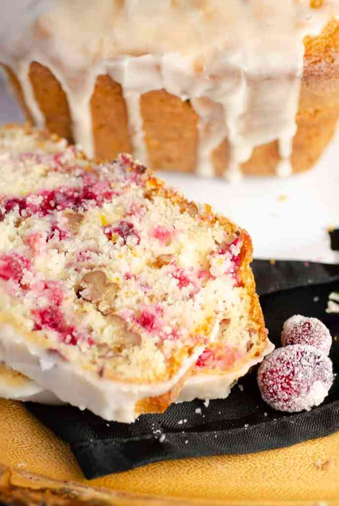 Two slices of Frosted Cranberry Nut Bread up close to show the color and texture.