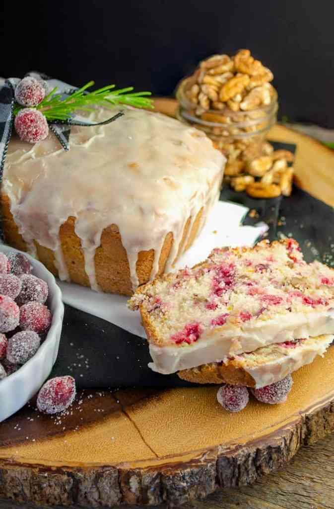 A loaf of Frosted Cranberry Nut Bread sits on a table surrounded by slices of cut bread, sugared cranberries, whole pecans and sprigs of green rosemary.