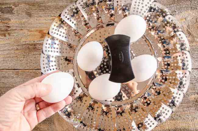 Raw eggs are placed into a metal collapsible steamer basket to make Easy-Peel Boiled Eggs.