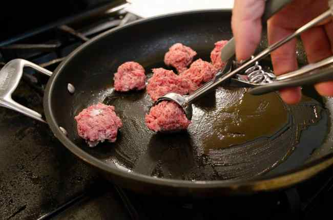 Raw meatballs being placed into a skillet with a small ice cream scoop.