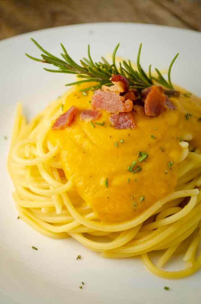 A closeup picture of a bed of spaghetti smothered in Winter Squash Pasta Sauce garnished with crumbled bacon, chives and a sprig of rosemary.