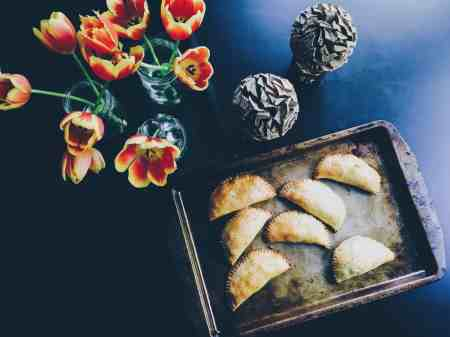 Empanadas, a Latino heritage recipe, are handheld meat pies either baked or fried, filled inside with savory meet fillings like pork, chicken or beef seasoned with savory spices, tomatoes, and vegetables like potato and sometimes cheese.