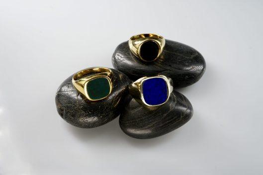 Siegelringe in unterschiedlichen Metallen. Hinten mit Lagenonyx, vorne links mit Heliotrop und vorne rechts mit Lapis-Lazuli