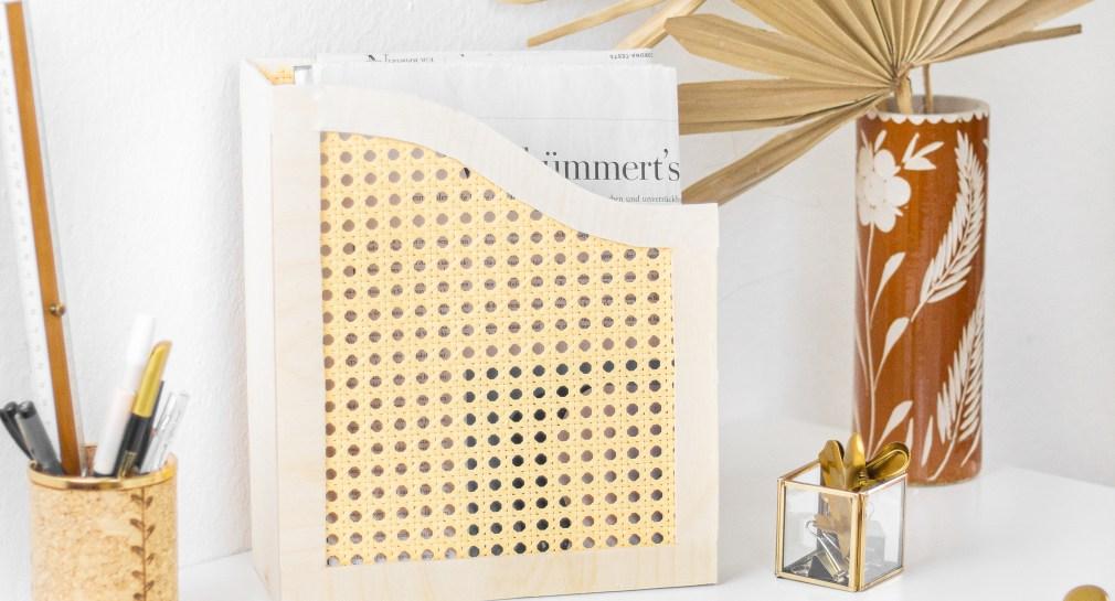 Der DIY Schreibtisch Organizer aus Holz und Wiener Geflecht steht mit einigen weiteren Schreibtisch-Utensilien, einem Block, einer Klammer, einem Stiftehalter aus Kork und einem Bleistift, auf einem weißem Schreibtisch, dahinter steht eine terrakottafarbene Vase mit getrockneten Palmblättern.