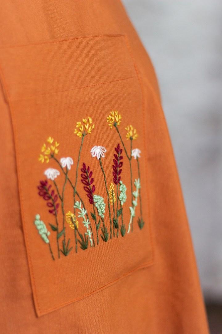 Eine Nahaufnahme der Tasche der orangenen Schürze mit gestickten Blumen.