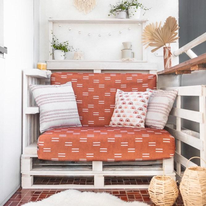 Vollendetes Balkon-Makeover: die Paletten sind weiß gestrichen, die Polster wurden in rostrotem Stoff neu bezogen und die Sitzecke wurde mit Pflanzen und Makramee dekoriert.