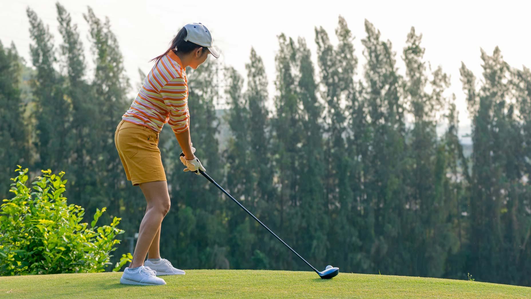 women's golfer hits ball