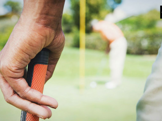 men holding a golf club grip with a course background