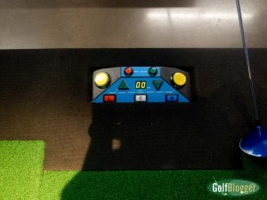 The floor console at X-Golf Ann Arbor controls ball delivery to the hitting zone, tee height and aiming. It also lets you know whether you hit the ball fat or thin.