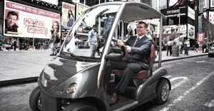 man in suit driving street legal golf cart in Manhattan